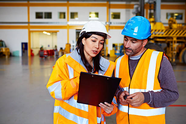 Shot of two warehouse workers talking together over a clipboard while standing inside of a large warehouse